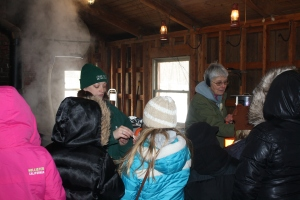LCMP Staff and volunteers handing out maple syrup samples in our Sugar Shack